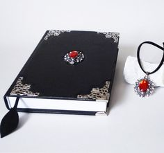 #Set of two black #leather witch notebook #journal with an awesome red pendant in middle, and the same red glass pearl on a black vegan suede leather necklace... Leather Gifts, Suede Leather, Black Leather, Leather Necklace, Leather Jewelry, Leather Photo Albums, Leather Diary, Handmade Notebook, Accessories