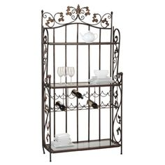 Claremont Baker's Rack - Bronze -  An elegant dining area storage option. Gold highlights for the Claremont, a bronzed metal baker's rack that holds a case and half of 750ml bottles. Three glass-lined shelves to display serving pieces, dinnerware and stemware. Intricate scrollwork at top and sides.