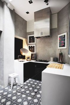 Tiny kitchen, concrete walls, black and white, hydraulic floor tiles.