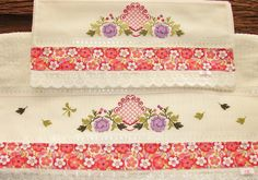 Jogo de banho bordado manualmente em ponto de cruz.  Barrado em tecido 100% algodão e bordado inglês.    As cores da toalha e bordado podem ser alteradas conforme sua preferência.  As toalhas são personalizadas com o nome.    OBS: O tecido floral pode variar, de acordo com a quantidade em estoque...
