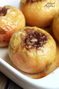 The front corner of a casserole dish with baked apples filled with sugar mixture.