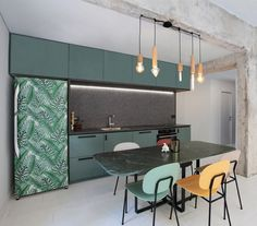 This #kitchen designed by #NaamaAtlan in #TelAviv, #Israel balances the industrial look of the raw textured concrete walls out with a modern aesthetic using a contemporary chandelier, bright chairs and bold looking refrigerator.