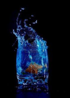 Orange in blue water splash on black background