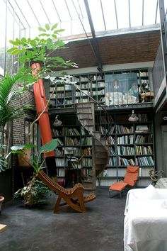 Floor to ceiling bookshelves, a spiral staircase, a glass roof letting in tons of natural light, greenery, AND a giant fountain pen - so perfect.