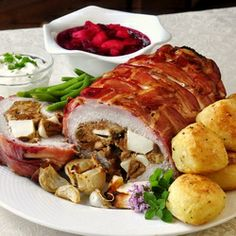 Apple and Almond Stuffed Pork Loin in a Bacon Blanket, served with roast potatoes and cranberry apple sauce. One great autumn meal.