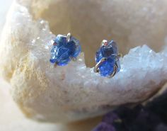 A pair of raw, natural blue freeform tanzanite nuggets have been set into sturdy handmade sterling silver settings. Each pair is unique and