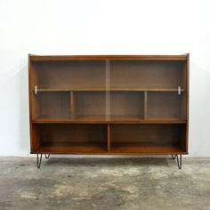 1960s Danish modern style bookcase with glass sliding doors, multiple shelves, and hairpin legs