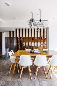 Comedor de un departamento en Palermo con tirantes de madera hasta el cielo raso que lo divide de la cocina. Además, mesa extensible (Bacano) y lámparas de techo en varias formas geométricas.