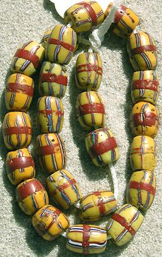 Venetian old trailed French Cross African Trade beads   oval beads with a yellow body, trailed vertical black, white and red lines and a horizontal red band around the center.