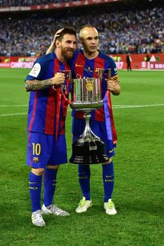 Barcelona's Argentinian forward Lionel Messi (L) and Barcelona's midfielder Andres Iniesta hold up the trophy after the team won the Spanish Copa del Rey (King's Cup) final football match FC Barcelona vs Deportivo Alaves at the Vicente Calderon stadium in Madrid on May 27, 2017..Barcelona won 3-1. / AFP PHOTO / Ander GILLENEA