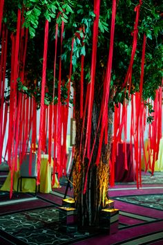 Before entering the reception, wedding guests were encouraged to secure their well wishes to the couple on red ribbons suspended from a wishing tree constructed of birch and willow branches. #weddingwishes #tree #ribbons Photography: Davina + Daniel. Read More: http://www.insideweddings.com/weddings/vibrantly-colored-indian-wedding-in-new-orleans-lousiana/579/