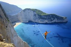 A man walks a slackline over Navagio Beach in Zakythos, Greece, in this National Geographic Your Shot Photo of the Day.