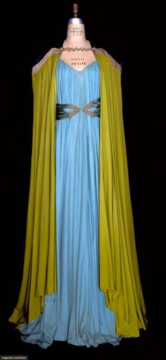 """Both knit silk & labeled """"Elizabeth Hawes Inc."""": sky blue trapeze shaped dress, rouleau shoulder straps & 2 pleated front panels attached at front neckline, pink silk faille petticoat; pea green cape w/ blue satin curving yoke bordered by woven goldmetallic & mushhroom silk band, CB narrow insert of blue satin, blue satin belt"""