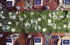 drape a sheet of moss down the table and accent with natural elements, like twigs and flowers.