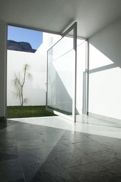 12 Pivot Doors Leading To Patios: Mexican firm Dear Architects' 4 Plan House in Santa Cantarina, Mexico is a four-level, minimalist structure with luminous light effects. Here, a large glass pivot door on a stainless steel frame opens onto a walled, grassy area with a lone tree.