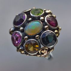 Dorrie Nossiter. Arts and Crafts ring.  Gold, silver, opal, tourmaline, peridot, citrine and garnet, c. 1930. Diameter: 1.90 cm (0.75 in). Ring case. Sold by Tadema Gallery. View 1.