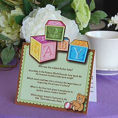The Baby Table Tents features an adorable baby block design with a brown teddy bear and his ball on a mint green background.