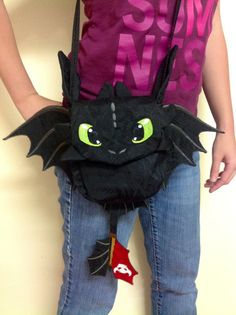 A playful long strap purse of Toothless the Night Fury. His eyes, wings, and tail are machine embroidered with my on digitized design and just