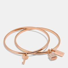 Petite key, padlock, and hangtag charms add playful polish to a sophisticated bangle set plated in precious metal and accented with brilliant Swarovski crystals. Made to stack or wear alone, each piece comes hallmarked on the inside with the Coach logo.
