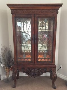 ASHLEY FURNITURE COMPANY 7 FT. CARVED CURIO CABINET WITH MIRRORED BACK, GLASS SHELVES, METAL OVERLAY ON THE DOORS AND CARVED ACANTHUS LEAF AND SHELL DESIGN.