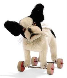 A STEIFF BULLY ON WHEELS, (1328,2), black and white mohair, brown and black glass eyes, velvet muzzle, black stitching, horsehair collar, red painted wooden wheels, white chest tag with metal rim and FF button, circa 1929 --11½in. (29.5cm.) long (some thinning to forehead and lower half of metal rim missing from tag)