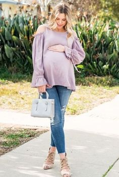 Solid cold shoulder maternity top. Rounded neckline. Long sleeves with ruffle trim and tie accent. This style was created to be worn before, during, and after pregnancy.