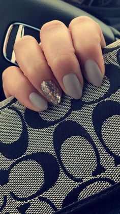 Matte grey nails with silver and gold glitter accent nail.