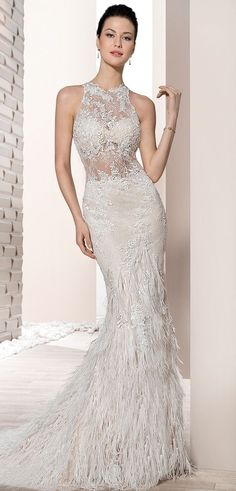This alluring fit n flare Halter gown features delicate Venice lace with sheer touches on the bodice, a plunging low back and a flared feather skirt flowing into a Sweep train.