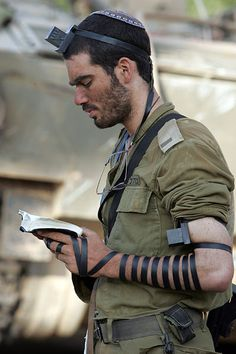 Israeli soldier praying with tefillin. Hes taking scripture literally! Deuteronomy 6:8 And thou shalt bind them for a sign upon thine hand, and they shall be as frontlets between thine eyes.