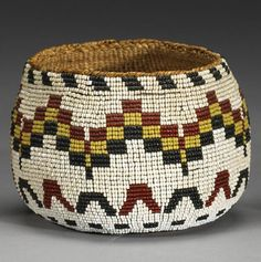 A Modoc beaded basket || The softly woven rounded sides and base fully covered in a loom-beaded panel, showing checkered, chevron and hatchmark bands on a white background, concentric rings on the base.