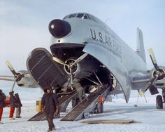 A wheeled Douglas C-124 Globemaster unloading on a snow runway at McMurdo Station, Antarctica, to deliver a smaller ski-equipped plane in 1956. Photo by Jim Waldron.