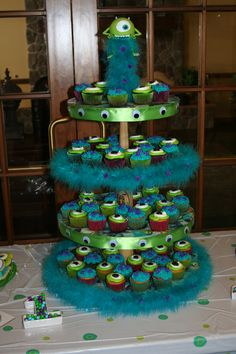 "Monsters Inc cupcake stand Took my baseball cupcake stand and converted it to use for grandson's birthday party!  Added green ribbon with eyes and teal fur for edging, Monsters Inc wrapping paper covered the wood rounds.  Found a Mike Wazowski ""punching ball"" and cut the bottom so he would fit over the baseball topper!  Wish I had covered more with fur in between rounds.  The fur had purple fuzz balls glued on it to get that Sully look!"