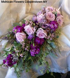 A cascade bouquet of lavender roses purple stock and wax flower accents makes a stunning look on trend for 2015's return of the cascades
