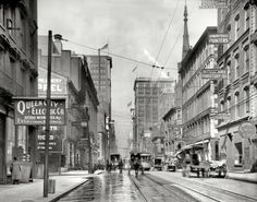 """Circa 1910. """"Fourth Street, Cincinnati, Ohio."""" Home to merchants trading in a variety of goods and services, the most esoteric of which might be """"Ostrich Feathers & Boas, Cleaned, Dyed and Curled."""""""
