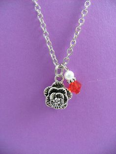 Simple chain necklace features a silver rose and a red and white bead dangle.  Decorative three dimensional rose charm (5/8 diameter) is accompanied by white glass pearl and red Swarowski crystal bead strand. 17 inch necklace, base metal lobster clasp. Officially licensed product.  Perfect gift for the AOPi sorority girl, features the color and symbol of the sorority. Also great gift for the flower lover, a friend named Rose or just because!  Please let me know if you need any adjustment...