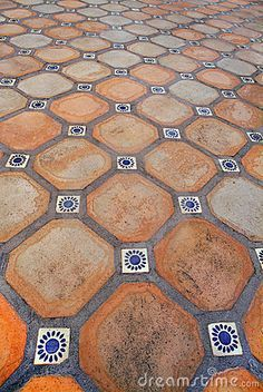 Terracotta square tiles with chamfered corners, infilled with small blue Spanish tiles - good idea to make small finacy tiles go a long way