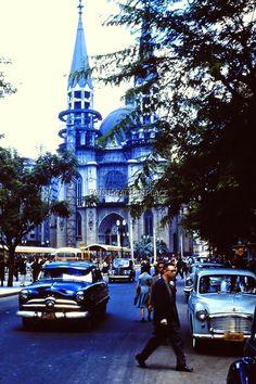 """SÃO PAULO EM 1955 A foto colorida, preciosidade para aqueles idos de 1955 com a qualidade de seu registro, mostra a Praça da Sé, em São Paulo, com sua conhecida Catedral da Sé, uma das belas construções históricas da cidade. Enquanto um transeunte atravessa a rua, um Ford 1949 percorre a rua, mostrando um acessório de proteção chamado """"chapéu de sol"""", enquanto, estacionado, aparece um Hillman Winx 1954 com um azul prateado."""