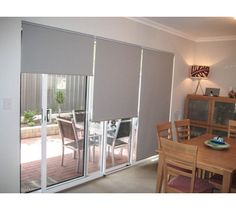 Blockout fabric in Combo Grey. 3 rollerblinds on a large sliding door. Each blind individually controlled. Inside mount & front rolled to allow room for the door handle.