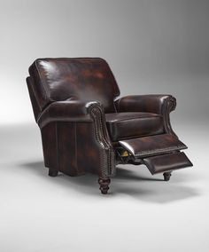 Plush and luxurious, the Lexington Reclining Armchair features a variety of upscale style details, including nailhead trim, pleated side panels, sloping arms and turned wood feet. The chair is shown here is a distressed Buckeye leather.