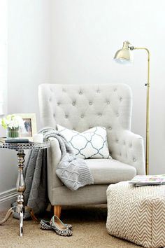 cosy reading nook with tufted grey armchair and silver steel round side table