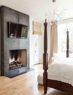 Chic bedroom features a white plank ceiling accented over wood 4 poster bed facing a sleek black ...