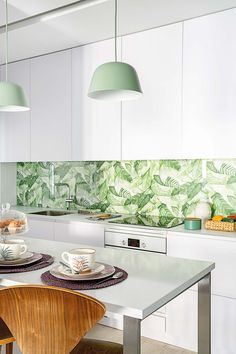 a modern tropical kitchen with sleek white cabinets, a tropical leaf print backsplash, green pendant lamps and wooden chairs - DigsDigs Botanical Kitchen, Botanical Interior, Tropical Interior, Modern Tropical, Blue Kitchen Cabinets, White Kitchen Island, White Cabinets, Wooden Dining Tables, Dining Nook