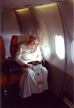In his early papacy, Blessed John Paul II often traveled outside of Rome. He would sit on the plane catching up on reading or praying the Divine Office. #FunFriday #CountdowntoCanonization #Shepherd1 Photo Credit: L'Osservatore Romano