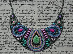 Collier fantaisie de type plastron vert/bleu/rose/jaune, composé de 3 belles pièces articulées en métal argenté, rehaussées de petits cabochons, perles, strass et d' un joli palet craquelé en céramique verte.