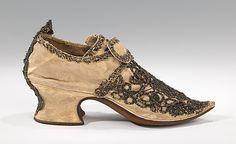 1690–1729 - Provavelmente Britânico. Estilo Barroco, o bordado sobre este par de sapatos de senhora Latchet é extremamente robusto, tridimensional e complexa, utilizando várias formas diferentes de fio metálico e rendas ouro. Como o século avançava, mais suave estilo rococó francês. O dedo do pé ponto extremo visto neste exemplo é um elemento que persistiu desde o final do século 17, e é combinado aqui com o salto mais baixo, atarracado típico de sapatos britânicos do início do século 18.
