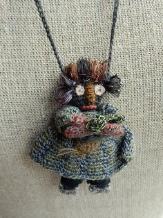 Hand crocheted doll approximately 2.5 nches tall on a 24 inch crocheted chain, merino wool.