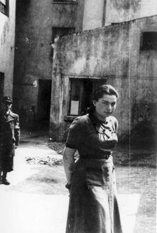 Lodz, Poland, A girl in the ghetto, with a Jewish policeman in the background.