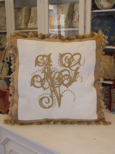 Cuscino barocco con monogrammi monocromatici oro.