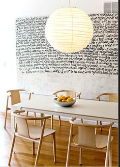 Second view, Neruda poem inscribed on dining wall. Wood chairs white table combo.