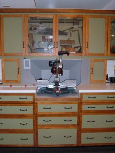 Mitre saw bench...looks like built in dust collection hood incorporated with more cabinets. Sick!